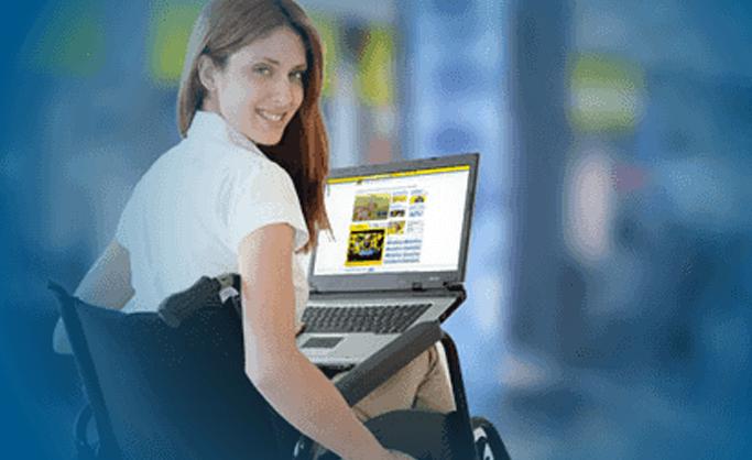 Mulher sentada em cadeira de rodas, com notebook apoiado em suas pernas, no site do Financiamento do Banco do Brasil