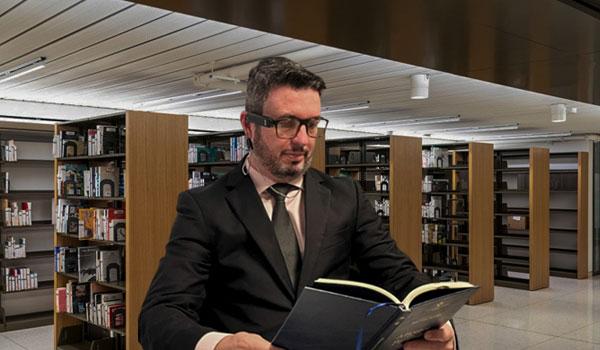 Dr Richard Portela, advogado, deficiente visual, está lendo um livro com o auxilio do dispositivo OrCam MyEye