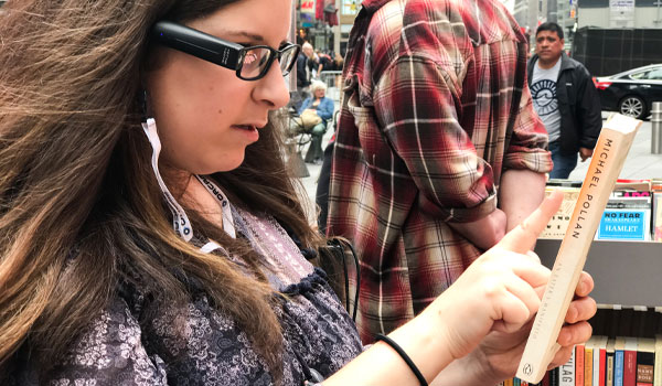 Zoe Hartman lendo a capa de um livro com o dispositivo OrCam MyEye em Nova York